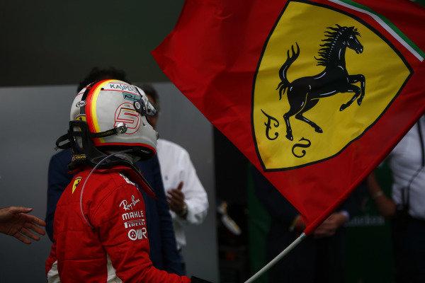 Sebastian Vettel, Ferrari, 1st position, waves the Ferrari flag in Parc Ferme.