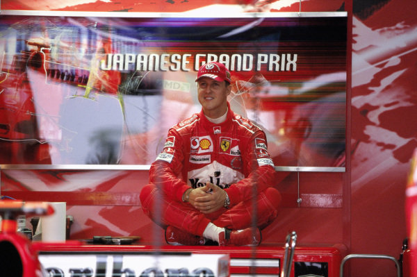 Michael Schumacher sits at the back of the garage.
