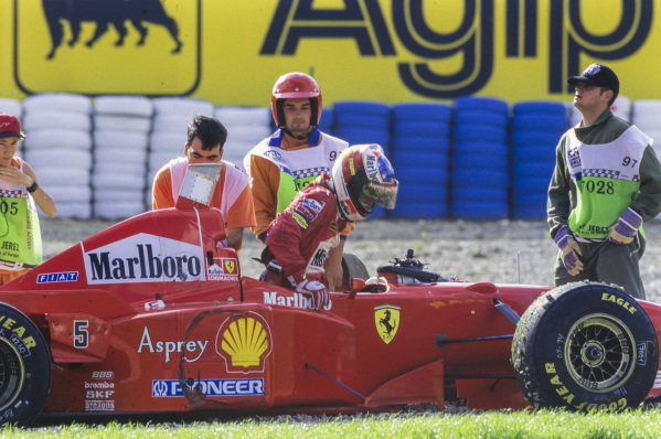 Marshals attend to Michael Schumacher, Ferrari F310B, after his controversial collision. Tyre marks can be seen on the sidepod of the Ferrari.