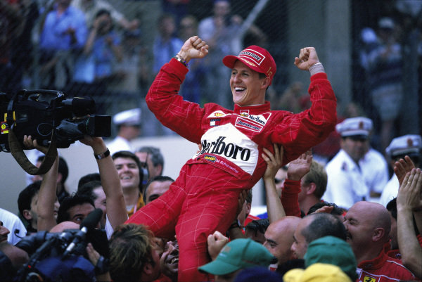 Michael Schumacher celebrates as he is raised in the air by the Ferrari team.