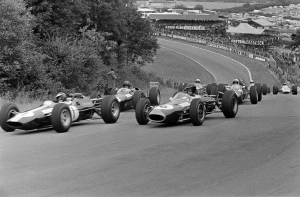 Jim Clark, Lotus 25 Climax, alongside Dan Gurney, Brabham BT7 Climax, leading Graham Hill, BRM P261, into Druids on the opening lap.
